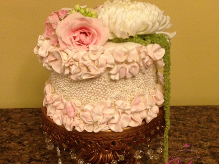 Ruffled Pearl Cake topped with flowers from NWA Florist